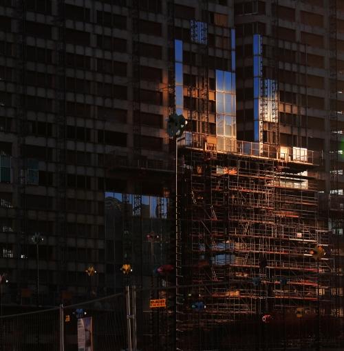 Le soleil couchant se reflète sur un immeuble en construction.