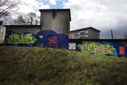 """Un local orné d'un graff dans un joli style """"comics"""", visible seulement depuis la cimenterie."""